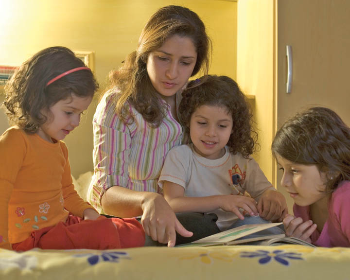 Mormon Mother reading about Jesus with young children.